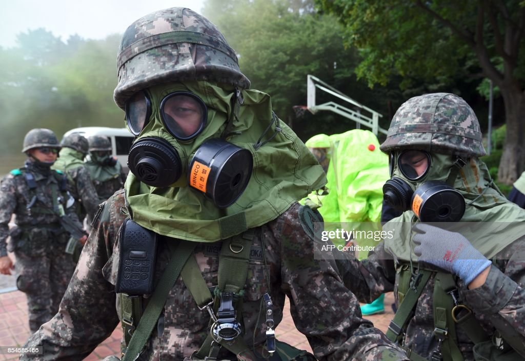 South Korean soldiers wear gas masks during a decontamination training at a stadium in Seoul on September 27, 2017. The training is designed to train their systems and capabilities to increase their preparedness to respond to chemical, biological and nuclear threats. Yeon-Je