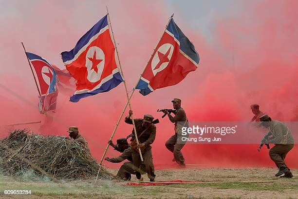 South Korean soldiers wear North Korea's military uniforms and hold North Korea's flags acting as North Korean soldiers as they take part in a...