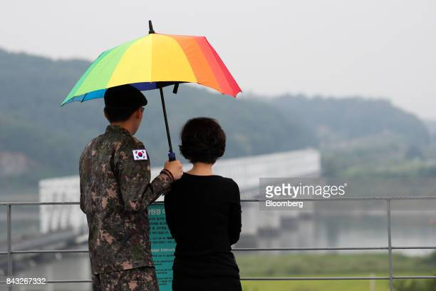 A South Korean solider holds an umbrella as he looks across to the north side of the border at the Imjingak pavilion near the Demilitarized Zone in...