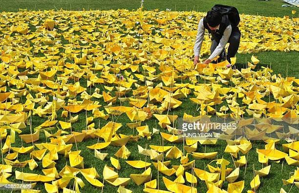 A South Korean student puts a yellow paper ship forming the shape of a heart at a memorial for victims of the 'Sewol' ferry in Seoul on May 7 2014...