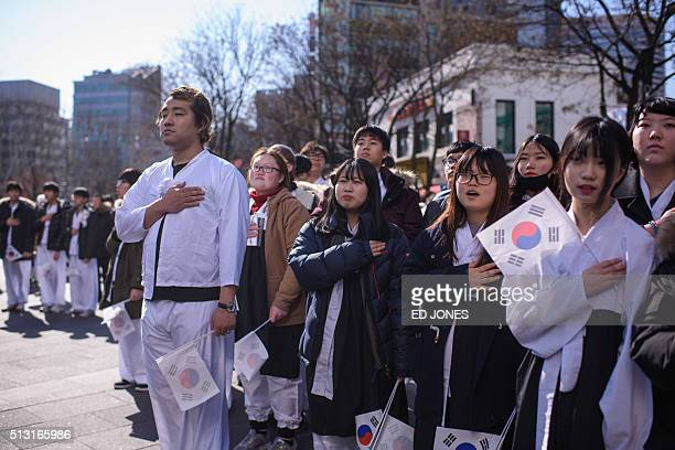 South Korean students gesture as they listen to their national anthem prior to an anti-Japan protest marking the 97th Independence Movement Day in...