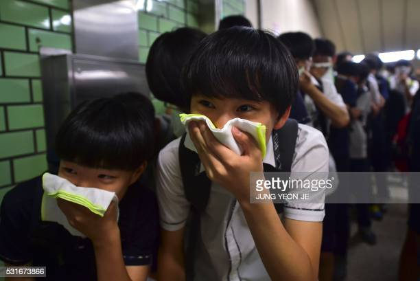 TOPSHOT South Korean students participate in a fire drill as part of a disaster management exercise at a subway station in Seoul on May 16 2016 South...