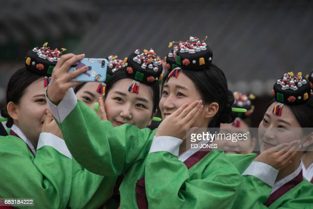 TOPSHOT South Korean students pose for a selfie following a traditional comingofage ceremony at Namsan hanok village in Seoul on May 15 2017 The...