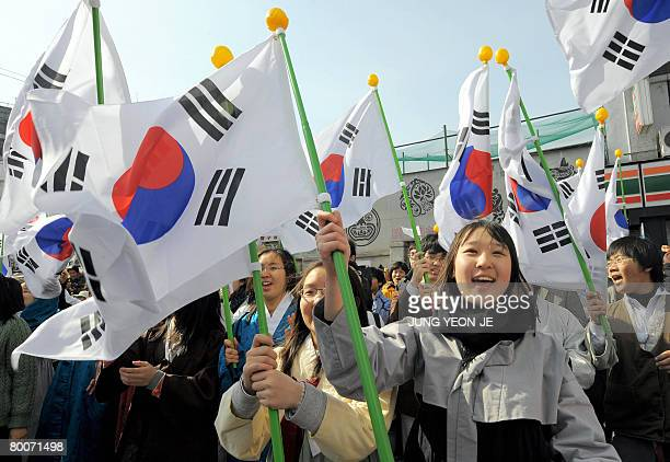 South Korean students wearing traditional costumes wave national flags to celebrate the March First Independence Movement Anniversary in Seoul on...