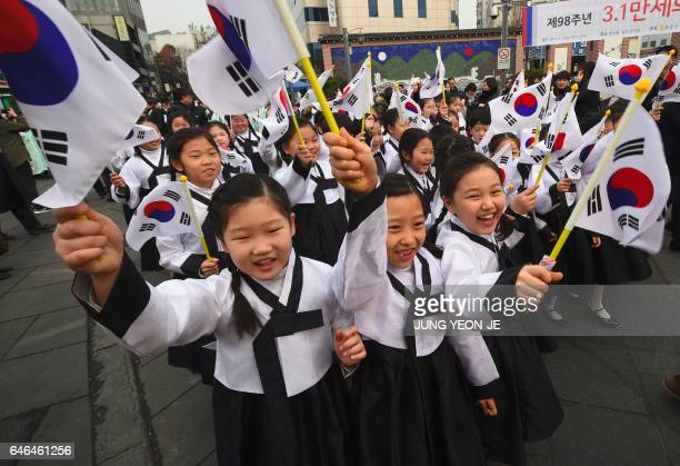 South Korean students wearing traditional costumes wave their national flags during celebrations of the 98th Independence Movement Day in Seoul on...