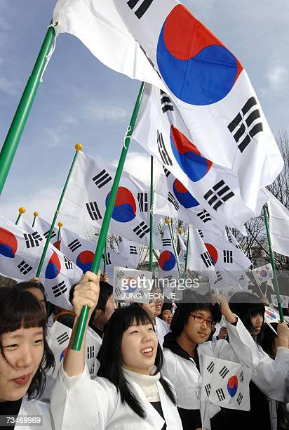 South Korean students wearing traditional Korean costumes wave national flags to celebrate the March First Independence Movement Anniversary in...
