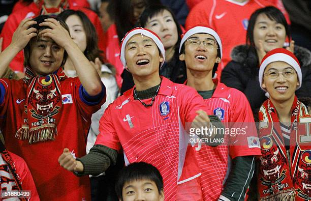 South Korean supporters celebrate after their team's victory over Germany in their friendly football match, 19 December 2004 at the Busan Asiad Main...