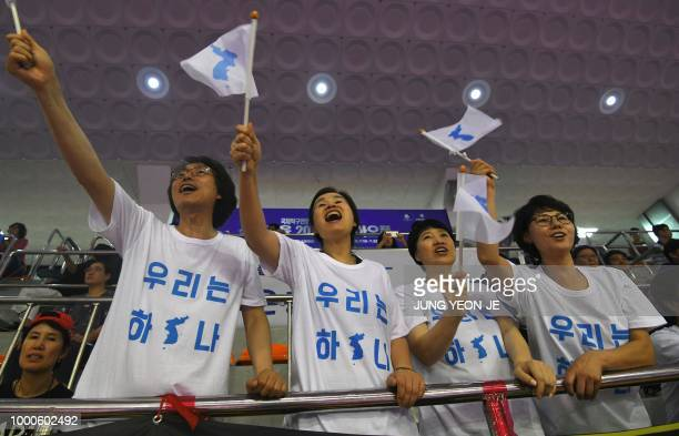 South Korean supporters for the united Korea team wave 'Unification flags' as they watch the preliminary round of the International Table Tennis...