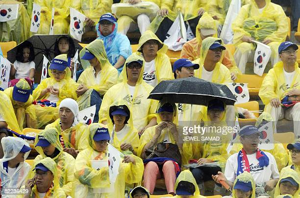 South Korean supporters wearing waterproofs watch their team shooting during the Women's Archery competition of the Beijing 2008 Olympic Games on...