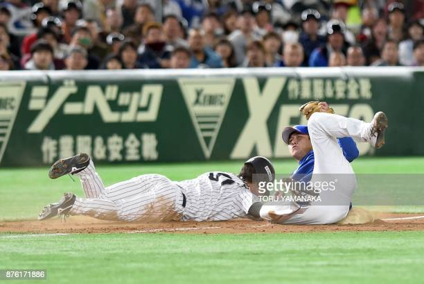 South Korean third baseman Jung Hyun slides to tag out Japanese outfielder Seiji Uebayashi at the fourth inning during the Asia Professional Baseball...