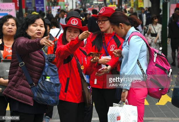 South Korean tourist information helpers guide tourists in the popular Myeongdong shopping district in Seoul on April 25 2017 South Korea's tourist...