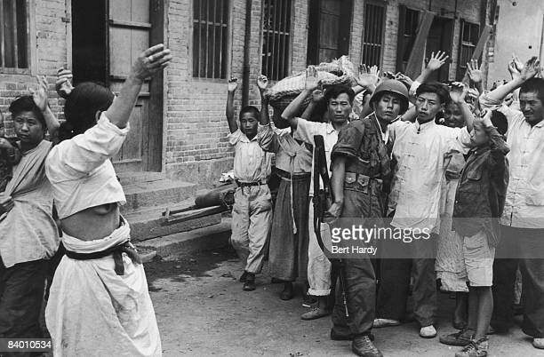 South Korean troops rounding up alleged communist sympathisers, following the American invasion and capture of the port of Inchon , Korea, during the...
