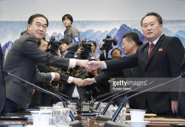 South Korean Unification Minister Cho Myoung Gyon shakes hands with Ri Son Gwon, head of North Korea's Committee for the Peaceful Reunification of...