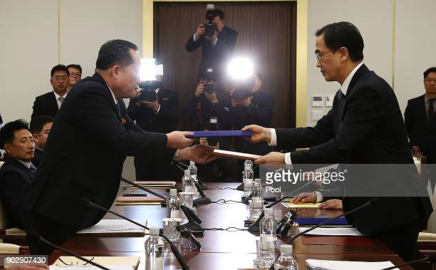 South Korean Unification Minister Cho MyoungGyon exchanges documents with the head of the North Korean delegation Ri SonGwon after their meeting at...