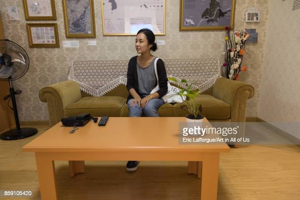 South Korean visitor sit on a sofa during the exhibition Pyongyang sallim at architecture biennale showing a north Korean apartment replica National...
