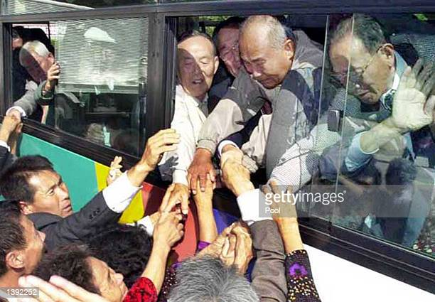 South Korean visitors in a bus try to hold the hands of their North Korean relatives as they leave for home after the fifth reunion meeting of...