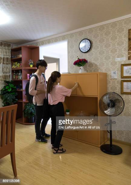 South Korean visitors looking in a cupboard during the exhibition Pyongyang sallim at architecture biennale showing a north Korean apartment replica...
