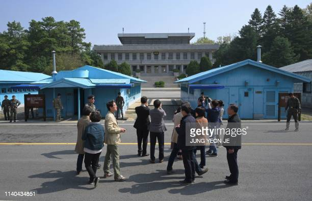 South Korean visitors stand on the South side during a public tour to the border truce village of Panmunjom in the Demilitarised Zone dividing the...