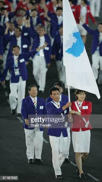 South Korean volleyball player Ku Minjing and North Korean former basketball player Kim Seong Ho carry a unification flag symbolizing one Korea...