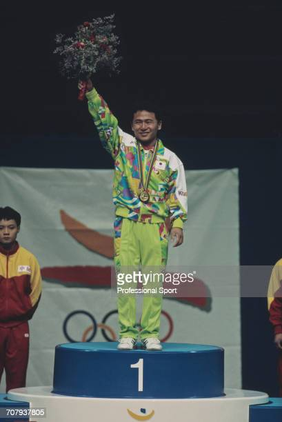 South Korean weightlifter Chun Byungkwan raises one arm in the air in celebration on the medal podium after finishing in first place to win the gold...