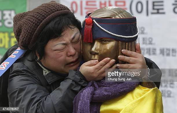 South Korean woman embraces the comfort women statue during an antiJapan rally in front of the Japanese embassy on February 22 2014 in Seoul South...