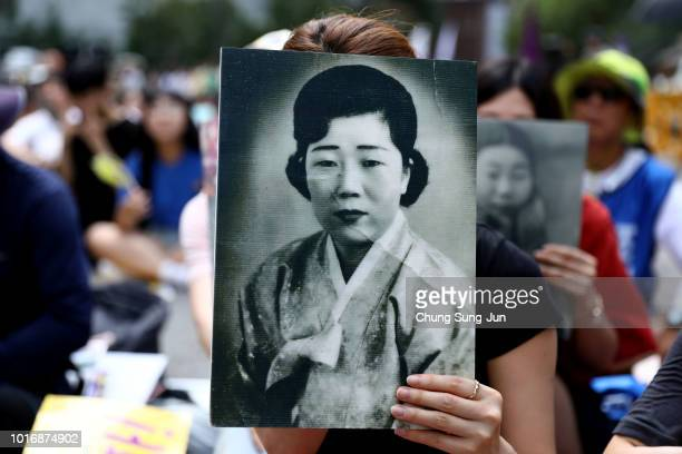 South Korean woman holds a portrait of deceased former South Korean comfort women during a rally to mark the 73rd National Liberation Day in front of...