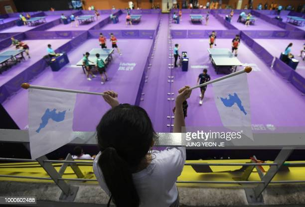 A South Korean woman holds 'Unification flags' as she watches the preliminary round of the International Table Tennis Federation World Tour Platinum...