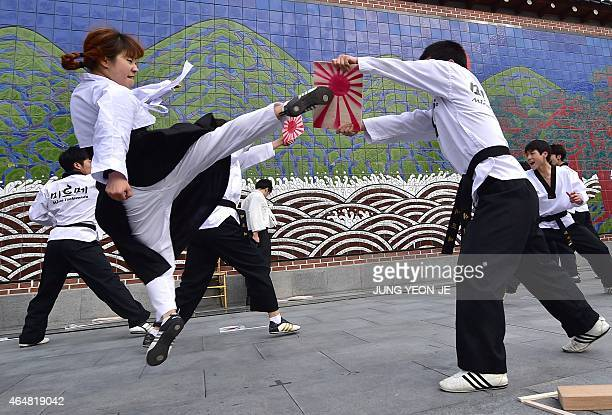 A South Korean woman kicks a board painted with the Rising Sun Flag during a Taekwondo performance in the celebration of Independence Movement Day in...