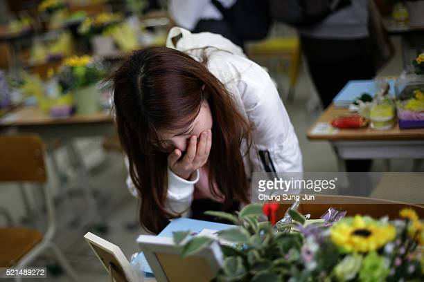South Korean woman mourns for victims of the Sewol ferry in a second year classroom at Danwon High School on April 16 2016 in Ansan South Korea In...