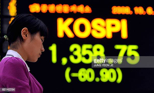 A South Korean woman sits in front of a stock index board at the Korea Exchange in Seoul on October 6 2008 South Korean shares closed 43 percent...