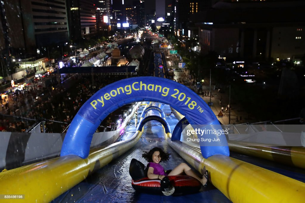 A South Korean woman slides down on an inflatable ring during the 'Bobsleigh In the City' on August 19, 2017 in Seoul, South Korea. The 22-metre-high 300-metre-long water slider has been set up in the central Seoul to promote upcoming PyeongChang Winter Olympics.