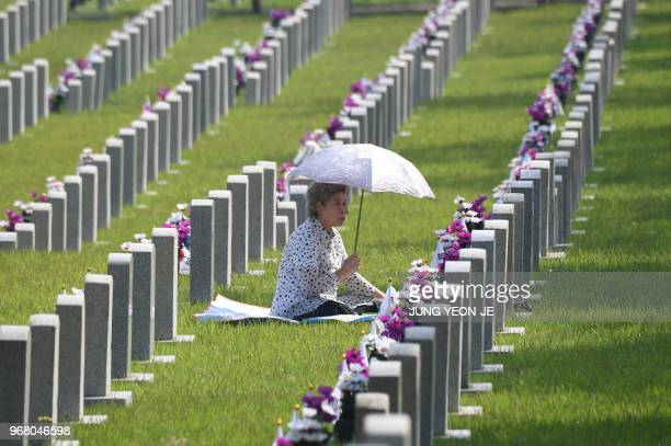 A South Korean woman visits the grave of her relative killed in the 195053 Korean War on the Korean Memorial Day at the National Cemetery in Seoul on...