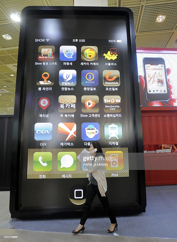 A South Korean woman walks past a smart phone-shaped advertisement during the World IT Show in Seoul on May 28, 2010.