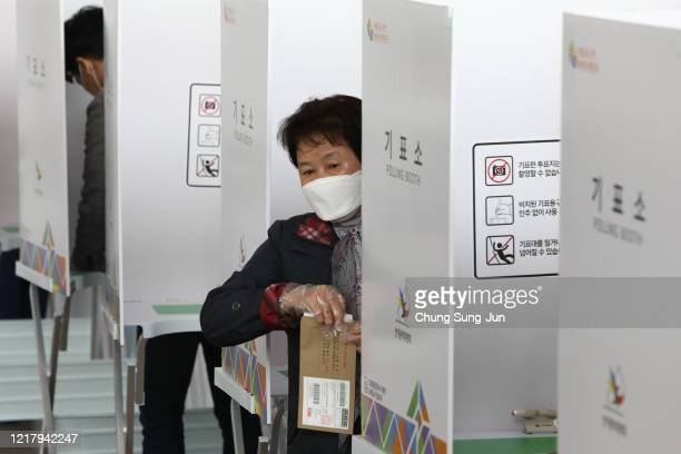 South Korean woman wears plastic glove cast his preliminary vote for Parliamentary election in a polling station on April 10, 2020 in Seoul, South...