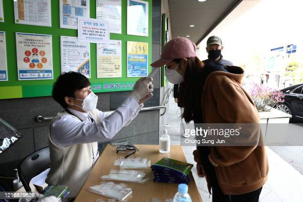 South Korean woman wears plastic gloves has her temperature checked upon his arrival to cast her vote for Parliamentary election amid the coronavirus...