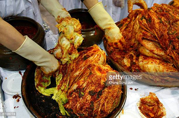 South Korean women make a Kimchi at a Kimchi exhibition November 6, 2003 in Seoul South Korea. Kimchi, Korea's national dish, has been in demand in...