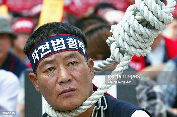 South Korean worker puts a noose around his neck to represent discrimination against irregular workers during an May Day protest in Seoul May 1 2003...