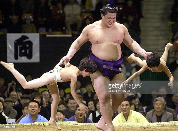 South Koreanborn sumo wrestler Kasugao entertains the crowd by lifting two young boys dressed in sumo attire up out of the ring prior to an...