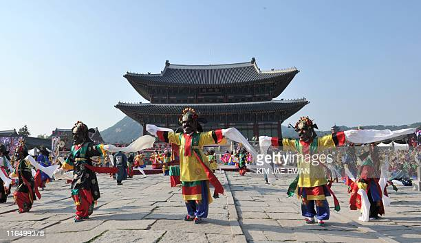 South Koreans attired in royal court costumes dance during a ceremony to welcome the return of priceless ancient royal books at Gyeongbok Palace in...