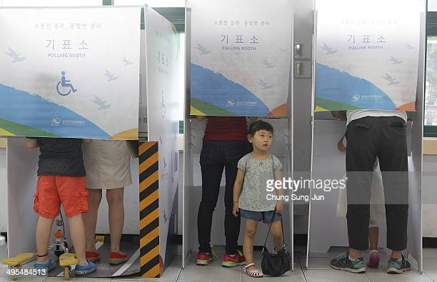 South Koreans cast their votes in a polling station on June 4 2014 in Seoul South Korea Seventeen provincial governors and mayors as well as...