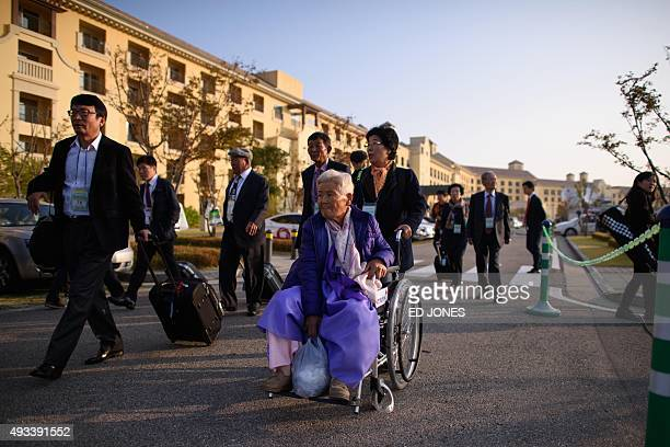 South Koreans chosen to attend a family reunion event with their North Korean relatives make their way to waiting busses outside their hotel before...