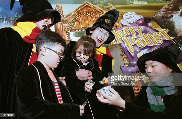South Koreans dressed as witches from the film Harry Potter and the Sorcerers Stone distribute candies to children December 14 2001 at a department...