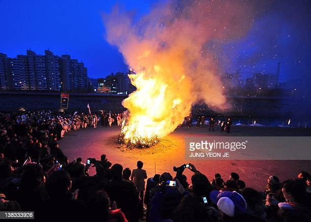 South Koreans gather around a huge bonfire to celebrate the first full moon of the Lunar New Year in Seoul on February 6 2012 Koreans traditionally...