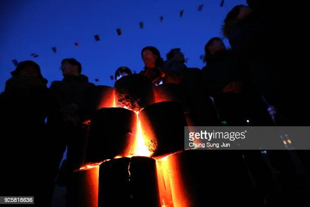 South Koreans gather around briquet fire during 'Jwibulnoli' a South Korean folk game on March 1 2018 in Seoul South Korea The event is part of a...