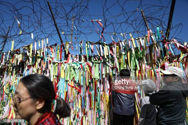 South Koreans hang ribbons wishing for reunification of the two Koreas on the wire fence at the Imjingak Pavilion near the demilitarized zone...