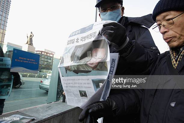 South Koreans hold up a special edition of a newspaper announcing the death of North Korean leader Kim JongIl on December 19 2011 in Seoul South...