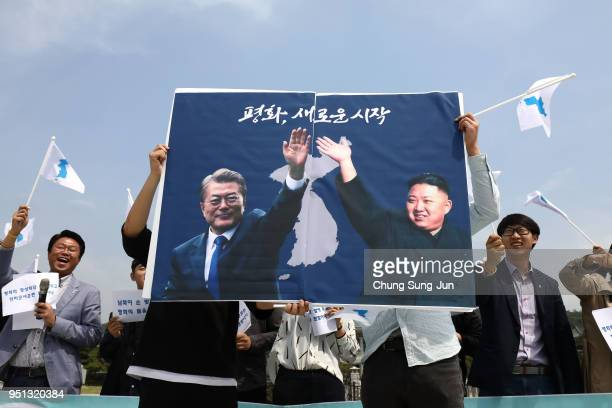 South Koreans hold up placards of South Korean President Moon Jae-In and North Korean leader Kim Jong-Un during a rally welcoming the planned Inter...