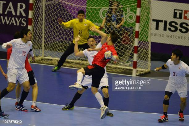 South Korean's Jung Suyoung attempts a shot on goal as Japan's players look on during the men's handball preliminary Group B match between South...