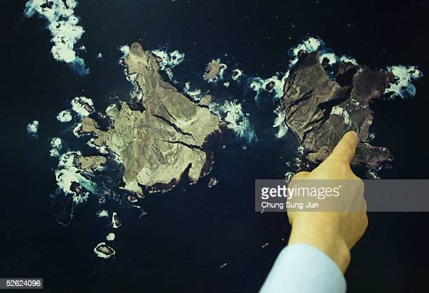 South Koreans look at a map of Ullung Island and the territorially disputed Dokdo islets at the map research institute on April 13 2005 in Seoul...