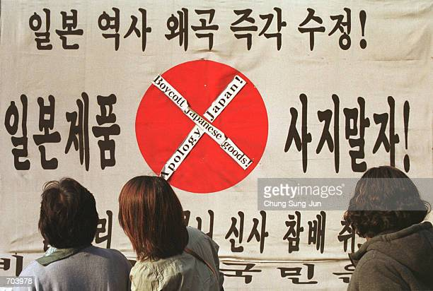 South Koreans look at antiJapanese writing on a Japanese flag during a rally to express anger over Japans 191045 colonial rule of the Korean...